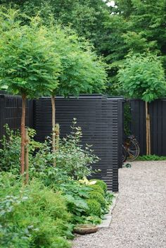 painted slat fence combined with a crushed gravel or stone walking path along the length of the wall