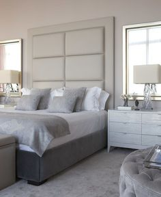 cool grey and white bedroom. upholstered headboard wall, mirrors flanking bed