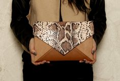 A clutch bag made of alcantara in toffi color and snake and camel synthetic leather . Inside cotton, patterned lining and a small zippered pocket.