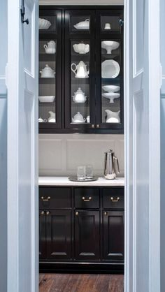 Butlers pantry reversw of kitchen black cabinets with white marble and white back splash