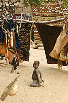 Baby in the middle of Bogolans - Bandiagara, Mopti - Mali