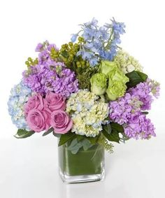 Lavender roses and spray stock, lime green roses, light blue delphinium and hydrangea, green hypericum & seeded eucalyptus in a cube.