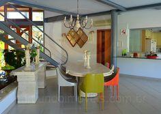 Localizada em um plano mais elevado, a sala de jantar possui mesa e aparador em mármore e oito cadeiras de design contemporâneo, em diferentes cores, para as refeições indoor.