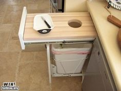 Cutting board (with hole in it) as a drawer with a slide-out trash can underneath it. Great idea for the kitchen. Even better if the cutting board surface is removable to easily wash it.