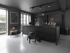 couleur cuisine tendance 2017 : meubles noir mat, chaise vintage en bois massif et sol en béton ciré