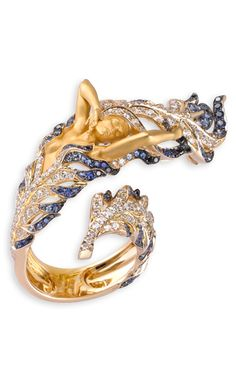 """Magerit - Hechizo Collection: Ring Odette: 18K gold, white diamonds, black diamonds, and blue sapphiires. The classic beauty of the famed Russian fairy tale, """"Swan Lake"""" is the common thread giving life to a collection marked by elegance and good taste. Delicate, soft and sinuous shapes enriched with strong volumes, textures and colour contrasts are the main features of this original performance in terms of artistic jewellery."""