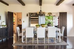 Exposed wooden beams and this stunning hardwood floor contrasts beautifully with the bright elements of this Los Angeles dining room.