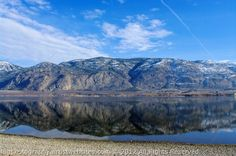 Mountains and a clear February Sky reflect off of glass like Osoyoos Lake.