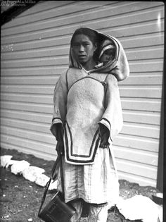 'Photo of an Inuit woman, probably from Baffin Island or Labrador, in a summerweight amautik with baby in the hood. Taken by Reginald Wilcox, probably in 1933.