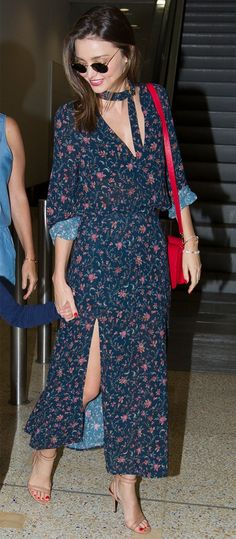 Miranda Kerr wears a floral midi dress with a red bag, round sunglasses, and nude sandals