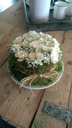 Cake Shaped Blooming ARRANGEMENT: |  On a Round Piece of Foam + Covered in Real or Craft Store Bought Moss + TOPPED with Dainty Babies Breath Flowers (...or add Daisies) AND White Roses + Set on a Plate + Tied with a Raffia Ribbon!  || Great for a Springtime Season Party, Easter Party, Tea Party, Alice in Wonderland Party, Simple Rustic-Chic Garden Party or Wedding, etc.