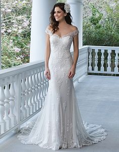 Show off your shoulders in this fit and flare tulle and point d'esprit gown with lace appliqués, illusion back, and Jersey lining complete with a chapel length train.