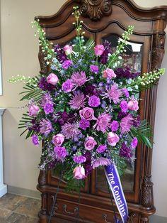 Lavender roses, spider mums, carnations, genestra, dark purple stock, light blue delphinium, purple monte casino, robillini, & leatherleaf standing easel spray by Donna Jeffries