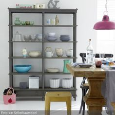 Um einen Landhausstil etwas zu modernisieren, kann man unterschiedlich farbige Möbel einsetzen. Dazu braucht man sich nicht gleich neue Möbel anzuschaffen – man kann ihnen auch einfach einen neuen Anstrich verpassen: Das grau gestrichene Küchenregal fügt sich perfekt in die Landhausküche, die sowohl rustikale Landhausmöbel als auch moderne Einrichtungselemente besitzt.