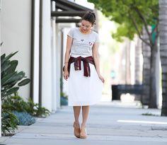 Look com t-shirt mescla com estampa e saia plissada branca para completar o look, Mule nude da Melissa. Para deixar o visual mais descolado a jaqueta amarrada na cintura dá esse ar mais despojado.
