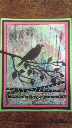 Gelli print background, die cut bird with branch, ribbon and brad that says Laughter.