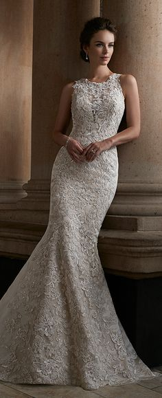 Lace trumpet wedding dress with illusion neckline. Sleeveless gown with high neckline, plunging sweetheart bodice, illusion lace back, court length train.