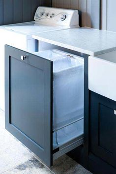 Under a white marble countertop fixed between a farmhouse sink and a top loading. Under a white marble countertop fixed between a farmhouse sink and a top loading washer this blue and white laundry room. Laundry Cabinets, Laundry Bin, Laundry Sorter, Laundry Room Storage, Small Laundry, Laundry Hamper, Hidden Laundry, Storage Organization, Shaker Cabinet Doors