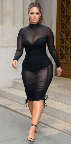 Ashley Graham showed off her enviable curves in this sexy ensemble: a bustier bodysuit layered under a skin tight sheer dress with ties at the hem. The supermodel accessorized with strappy leather sandals and silver hoop earrings.