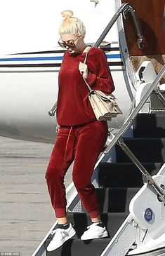 Chill:The make-up mogul sported a matching red velour crewneck sweater and jogging pants combination as she descended the private jet's steps on the runway