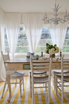 White sheer curtains and yellow striped rug in sunny dining room | Sally Breer