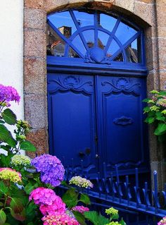 Gotta love the hydrangeas - with bold colored door, unusual transom