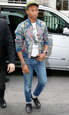 Pharrell Williams wears a graphic t-shirt, belted jeans, printed bomber jacket, and cool oxfords