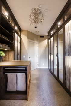 Walk-in closet with doors to cover all hanging clothing, and and island to store other items and pull-out laundry. Reach In Closet, Walk In Closet Design, Bedroom Closet Design, Closet Designs, Closet Island, California Closets, Custom Closets, Closet System, Laundry