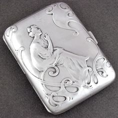 Fine Art Nouveau French silver cigarette case, circa 1890's. Decorated on the front with repousse, featuring a scene of a lady in a flowing gown with hair in a chignon, leisurely sitting in repose and smoking a cigarette while a dainty puff of smoke lingers overhead. The scene is surrounded by scrolling tendrils. Push button closure, opening to reveal a gold washed interior. From The Antique Boutique. www.theantiqueboutique.rubylane.com
