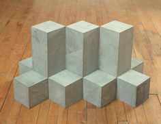 Carl Andre - Still Blue Range, 1989, Brussels, BelgiumBelgian blue limestone, 11 units; 3 vertical oblongs abutting edge to edge with 8 cubes, abutting face to face, on floor, 45 x 30 x 60cm