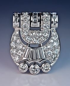 An Original Art Deco Diamond Clip / Brooch circa 1930 a handcrafted buckle-shaped platinum plaque with a white 18K gold clip / pin back densely set with sp
