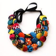 Handmade button necklace with African print fabric (Ankara). This necklace is multi colored. It is a statement piece that can compliment many styles. Tie