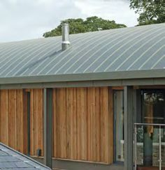 Vertical larch cladding and curved zinc roof of roughly the right radius.