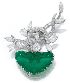 JADEITE AND DIAMOND BROOCH, 1950S. Designed as a flowering plant, the shoots set with pear-, marquise-shaped, brilliant-cut and baguette diamonds, the earth composed of carved and pierced jade, French assay marks.