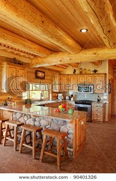 Log Cabin kitchen with breakfast bar with stone that matches the fireplace.