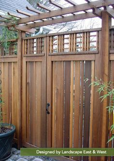 This tall cedar gate continues the fence line, while the arbor creates a striking accent.  Landscape East & West, Portland, Oregon
