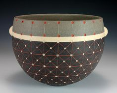 She uses different clay bodies, but you could emulate this with slip, then by painting underglaze on the bisqued form.
