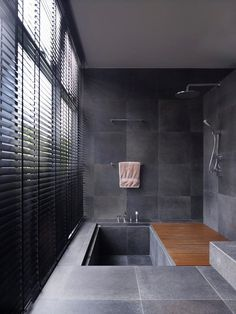 The timber deck on the shower area can slide over the sunken bath to increase the size of the space. The walls and floor are in a black homogenous tile and is matched with a dark stained timber venetian blind.