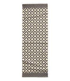 Rektangulært gulvtæppe i vævet bomuldskvalitet med trykt mønster på oversiden.