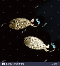 Gold earrings in the form of fish. Stock Photo