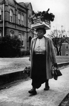 A woman carrying a crate of turnip greens balanced on her head, walks on the sidewalk during the Montgomery Bus Boycott, December 1, 1955, Alabama - The Montgomery Bus Boycott, a seminal event in the U.S. civil rights movement, was a political and social protest campaign against the policy of racial segregation on the public transit system of Montgomery, Alabama. The campaign lasted from December 1, 1955