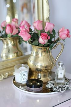 This gold vase with pink roses on your vanity.