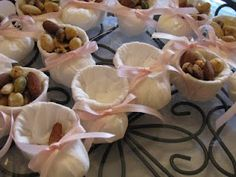 "Baby Shower idea - use a paper ketchup cup, a cotton ball, tissue paper and thin ribbon to make baby ""booties"".  Fill with m's, nuts or mints."