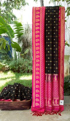 This black Benares kora has a pattern in Dijon yellow thread work and gold zari. The border is in magenta with a beautiful pattern in gold zari and the pallu has a similar pattern in magenta and go…