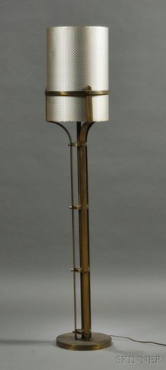 Art Deco Floor Lamp with Aluminum Shade c. 1940s Brass-plated metal stem rising from a circular base with single light fixture, in an industrial style, supporting the shade constructed from a sheet of punched aluminum.