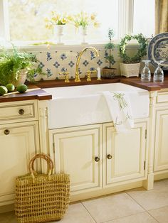Kitchen with blue and white backsplash, cream cabinets and farmhouse sink – Better Homes & Gardens
