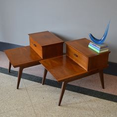 Heres a great pair of bi-level end tables manufactured by Lane in the 1960s. Each table is made of solid walnut with triangle inlay and feature