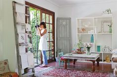 Una casa con estilo vintage moderno  En la caja contenedora blanca, el color lo aportan los objetos y el verde que entra por las ventanas. La biblioteca que domina el espacio es laqueada y hecha a medida, y la mesa ratona de Indonesia fue decapada en blanco por la dueña de casa