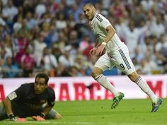 Real Madrid's French forward Karim Benzema and Barcelona's beaten goalkeeper Claudio Bravo after the French international scored during the Spanish league football match Real Madrid CF vs FC Barcelona at the Santiago Bernabeu stadium in Madrid on October 25, 2014