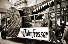 """Public displays of antisemitism in Nazi Germany took a variety of forms, from posters and newspapers to films and radio addresses. A float in the Fastnacht (Shrove Tuesday) parade in Singen am Hohentwiel features workers from the local aluminum cylinder works feeding """"Jews,"""" wearing paper noses, to the """"Jew Devourer,"""" a voracious crocodile. The motto carried by the workers' unit in the parade (not shown) was: """"Grumblers and Trouble-Makers go under the Roller."""""""